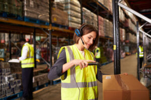 woman with headset scanning box in warehouse